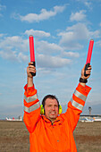 Airport ground crew signaling to aircraft, Airport Düsseldorf, North Rine-Westphalia, Germany
