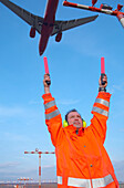 Airport ground crew holding up signaling sticks below approaching aircraft, Airport Düsseldorf, North Rine-Westphalia, Germany