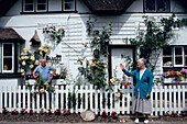 Neighbours greeting each other in front of a nicely restored cottage near Swampton, Hampshire, England