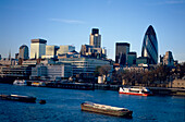 View over River Thames and pleasure boats to the Tower and City of London, including the Swiss Re Building.