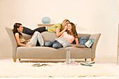 Three teenage girls (14-16) sitting on sofa and talking
