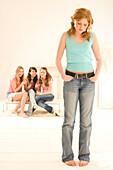 Weiblicher Teenager (14-16) steht Abseits von anderen Mädchen
