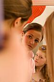 Teenage girl (14-16) applying make-up in mirror, sideview
