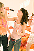 Teenage girls (14-16) singing into hair brushes