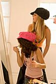 Two teenage girls (14-16) applying make-up in mirror