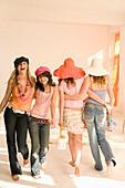 Four teenage girls (14-16) walking around, indoor