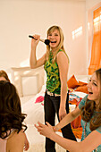 Girl (14-16) singing into make-up brush, three girls clapping hands