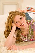 Teenage girl (14-16) lying on rug and smiling