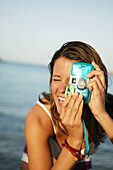 Young woman taking a picture with digital camera