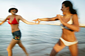Two young women running on the beach, laughing, blurred motion