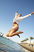 Woman leaping with arms outstretched, laughing