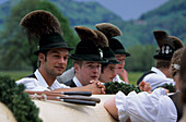 Four young men wearing hats with tufts of chamois hair at a maypole festival in Flintsbach, Upper Bavaria, Germany