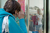 Young women looking at clothes in shop window