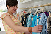 Young woman looking choosing dress from rack in clothes shop