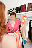 Young woman considering her friend for chosen dresses in a clothes shop