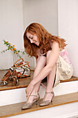 Young woman trying on shoes in shoe shop