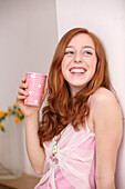 Portrait of young woman smiling with cup in her hand