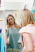 Young woman looking ad dress in mirror of clothes shop