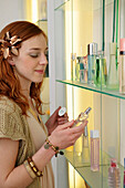 Young woman testing perfume in shop