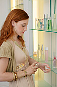 Young woman testing perfume in shop, Young woman testing perfume in shop