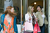 Young women walking out of shop with shopping bags, laughing