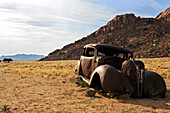 Wreck of an oldtimer car in the desert. Note the bullet holes. Klein-Aus-Vista. Gondwana Sperrgebiet Rand Park. Succulent Karoo Desert. Souther Namibia. Africa.