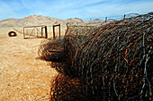 Old disused fence in the desert. It'll be taken down to give the wildlife a chance to migrate. Klein-Aus-Vista. Gondwana Sperrgebiet Rand Park. Succulent Karoo Desert. Southern Namibia. Africa.