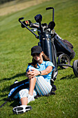 Young woman sitting on golf course leaning against golf bag