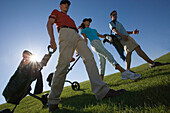 Group of people walking on golf course pulling golf bag on wheels, sideview, Apulia, Italy