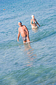 Senior couple go swimming in sea, Apulia, Italy