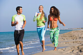 Three young people jogging on beach, Apulia, Italy