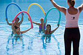 Trainer showing young people stretching exercises in pool, Apulia, Italy