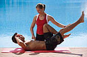 Female trainer helping man with stretching exercises, poolside, Apulia, Italy