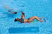 Woman lying on air mattress, man diving, Apulia, Italy
