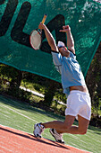 Male tennis player celebrating on court, arms outstretched, Apulia, Italy