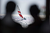 Two unrecognizable persons on beach, looking to sailboat on sea, Apulia, Italy