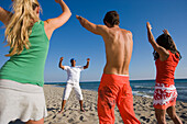 Group of young people exercising on beach with instructor, Apulia, Italy