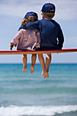 Two children sitting on bench before sea shore, boy hugging little girl, Apulia, Italy