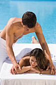 Young man massaging young woman on poolside, Apulia, Italy