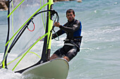 Young man windsurfing, Apulia, Italy