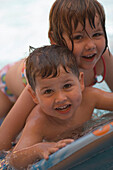 Two children playing in swimming pool, Apulia, Italy