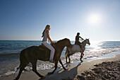 Young couple horseback riding at beach, Apulia, Italy
