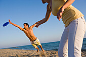 Young couple playing frisbee on beach, Apulia, Italy