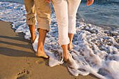 Young couple walking on beach, rearview, Apulia, Italy