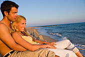 Young couple sitting on beach, sea shore, Apulia, Italy