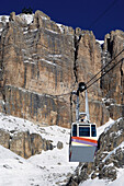 Overhead cable car in snowcovered  mountains, Passo Pordoi, Dolomites, Italy