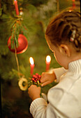 Girl (3-4 Years) decorating Christmas tree, hanging bauble on branch