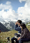 Japanese tourists photographing mountains, Zermatt, Switzerland