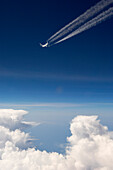 Aircraft with contrails flying over the clouds in front of a dark blue sky