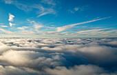 Cloud layer below blue sky